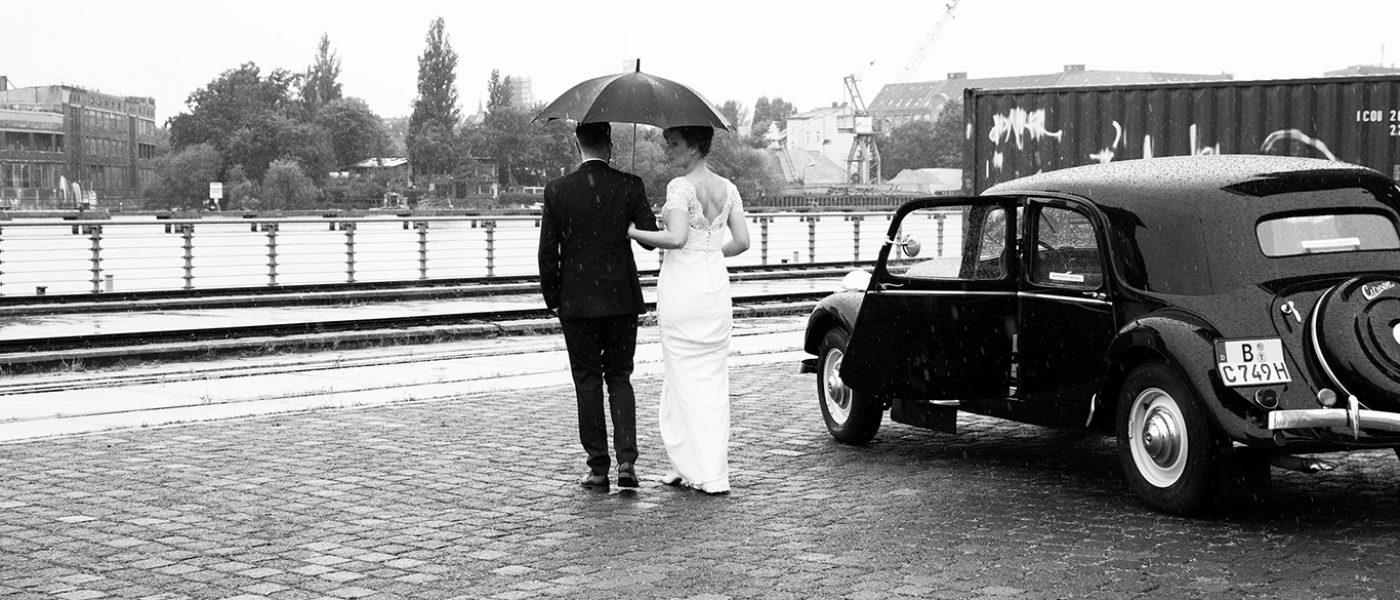 Ehepaar im Regen neben Oldtimer